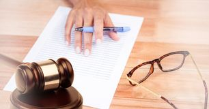 Gavel on desk with glasses and hand writing. Digital composite of Gavel on desk with glasses and hand writing Royalty Free Stock Photo