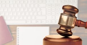 Gavel with keyboard and notebook in background. Digital composite of Gavel with keyboard and notebook in background Royalty Free Stock Photography