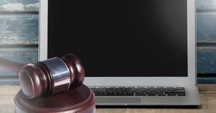 Gavel and laptop on desk. Digital composite of Gavel and laptop on desk Royalty Free Stock Photos