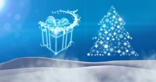 Gift box glowing and Snowflake Christmas tree pattern shape in snow landscape. Digital composite of Gift box glowing and Snowflake Christmas tree pattern shape Royalty Free Stock Photo