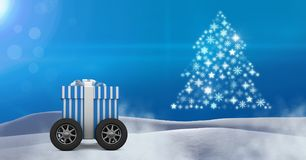 Gift box on wheels and Snowflake Christmas tree pattern shape in snow landscape. Digital composite of Gift box on wheels and Snowflake Christmas tree pattern Stock Photos