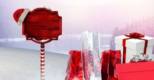 Gifts and Wooden signpost in Christmas Winter landscape and Santa hat. Digital composite of Gifts and Wooden signpost in Christmas Winter landscape and Santa hat Royalty Free Stock Photo