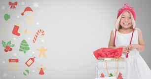 Girl against grey background with Christmas gift bag and Christmas illustrations. Digital composite of Girl against grey background with Christmas gift bag and Royalty Free Stock Photos