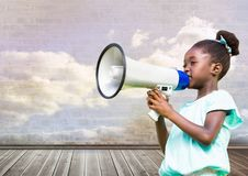 Girl with megaphone in front of cloudy room stock photography