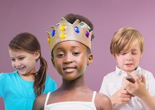 Girl wearing crown with friends in front of purple background royalty free stock photo