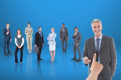 Hand choosing a business man on blue background with business people. Digital composite of Hand choosing a business men on blue background with business people Stock Photos