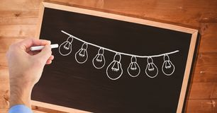 Hand drawing light bulbs on blackboard. Digital composite of Hand drawing light bulbs on blackboard Royalty Free Stock Photography