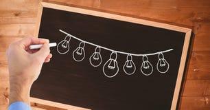 Hand drawing light bulbs on blackboard. Digital composite of Hand drawing light bulbs on blackboard royalty free stock photography