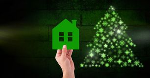 Hand holding home and Snowflake Christmas tree pattern shape glowing green. Digital composite of Hand holding home and Snowflake Christmas tree pattern shape Stock Illustration