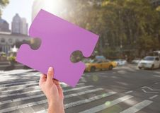 Hand holding jigsaw puzzle piece in city Royalty Free Stock Images