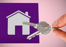 Hand Holding key with house icon in front of vignette. Digital composite of Hand Holding key with house icon in front of vignette Stock Image