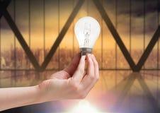 Hand holding light bulb by windows. Digital composite of Hand holding light bulb by windows Stock Photos