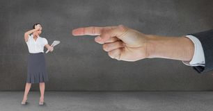 Hand pointing at surprised business woman against grey background Stock Photography