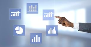 Hand touching business chart statistic icons. Digital composite of Hand touching business chart statistic icons Stock Photography