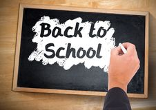 Hand writing back to school on blackboard. Digital composite of Hand writing back to school on blackboard Stock Photography