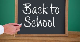 Hand writing back to school text on blackboard. Digital composite of Hand writing back to school text on blackboard Royalty Free Stock Photos