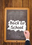 Hand writing back to school text on blackboard. Digital composite of Hand writing back to school text on blackboard Stock Images