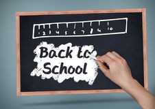 Hand writing Back to school text with ruler on blackboard. Digital composite of Hand writing Back to school text with ruler on blackboard Stock Image