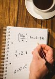 Hand writing math sums on notepad. Digital composite of Hand writing math sums on notepad stock photography