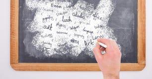 Hand writing school subjects on blackboard Stock Image
