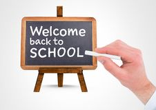 Hand writing Welcome back to school text on blackboard. Digital composite of Hand writing Welcome back to school text on blackboard Royalty Free Stock Photo
