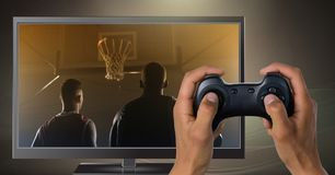 Hands holding gaming controller  with basketball players on television. Digital composite of Hands holding gaming controller  with basketball players on Stock Image