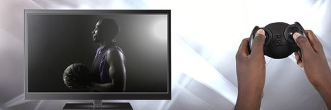 Hands holding gaming controller with basketball on television royalty free stock image