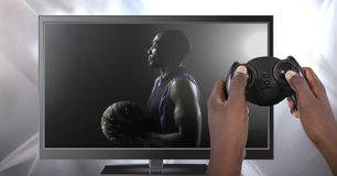 Hands holding gaming controller with basketball on television royalty free stock images