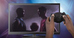 Hands holding gaming controller with soccer player on television royalty free stock images