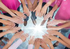 Hands together in circle over bright portal light with pink t-shirts stock photography