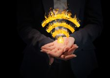 Hands with WIFI fire icon between. Black background Royalty Free Stock Photography