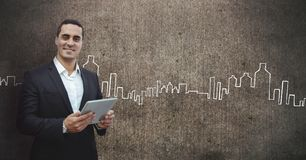 Happy business man holding a tablet against grey wall background with city icons Stock Photos