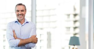 Happy business man standing against white blurred background Royalty Free Stock Image