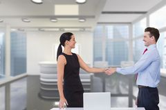 Happy business people shaking hands against office background Royalty Free Stock Photo