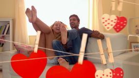 Couple jumping on a couch together. Digital composite of happy couple jumping on a couch together with hearts on a clothesline in the forefront. Couple having stock video footage