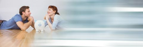 Happy couple lying on the floor with a piggy bank Royalty Free Stock Image