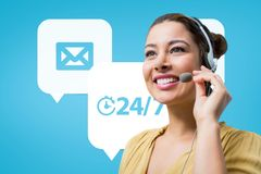 Happy customer care assistant woman against customer care background Royalty Free Stock Image