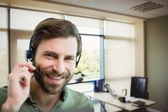 Happy customer care representative man against office background Stock Photography