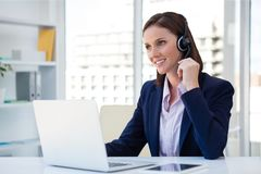 Happy customer care representative woman against office background Royalty Free Stock Photos