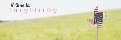 Happy labor day text and USA wind catcher in front of grass and sky Royalty Free Stock Photos