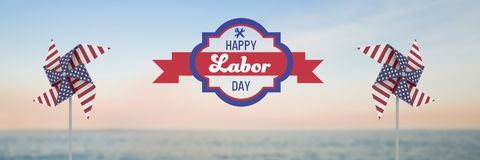 Happy labor day text and USA wind catchers in front of sea Royalty Free Stock Photo