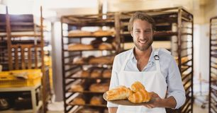 Happy small business owner man holding croissants. Digital composite of Happy small business owner man holding croissants stock photography