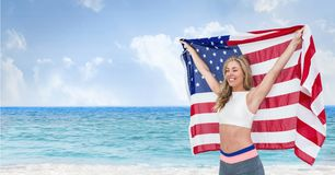 Happy woman holding a USA flag in the beach. Digital composite of Happy woman holding a USA flag in the beach Royalty Free Stock Image