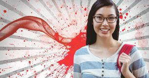 Happy young student woman standing against white and red splattered background. Digital composite of Happy young student woman standing against white and red Stock Image