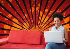 Happy young student woman using a computer against red, black and orange splattered background. Digital composite of Happy young student woman using a computer Royalty Free Stock Photos