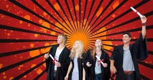 Happy young students holding diplomas against red, black and orange splattered background. Digital composite of Happy young students holding diplomas against red Stock Image