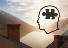 Head with puzzle piece icons over roofs by mountain lake. Digital composite of Head with puzzle piece icons over roofs by mountain lake Stock Photo