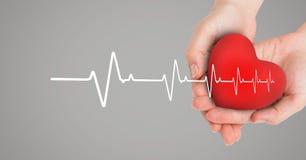 Heart beat over hands holding heart. Digital composite of Heart beat over hands holding heart stock images