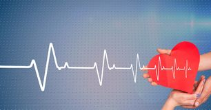 Heart beat over hands holding heart. Digital composite of Heart beat over hands holding heart royalty free stock image