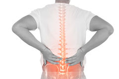 Digital composite of highlighted spine of man with back pain. Against white background stock photos